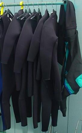 wetsuits hanging to dry