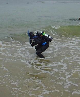 diver entering the water through the surf